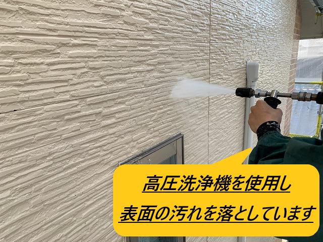 高圧洗浄機で外壁の汚れを落としている