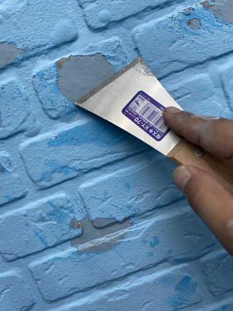 外壁を皮スキで擦っている様子